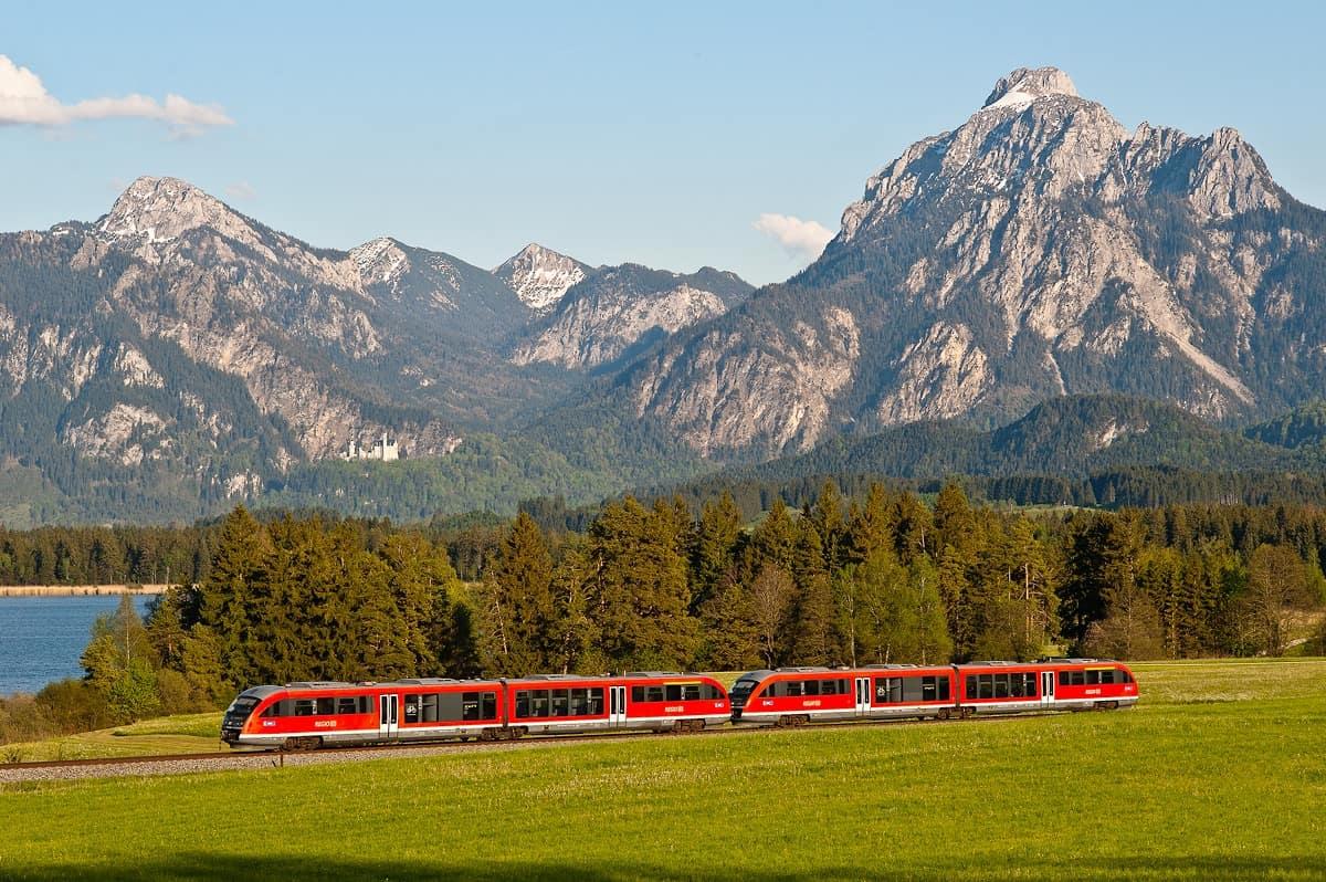 A train on the way to Füssen runs past Hopfensee with Neuschwanstein Castle in the background.