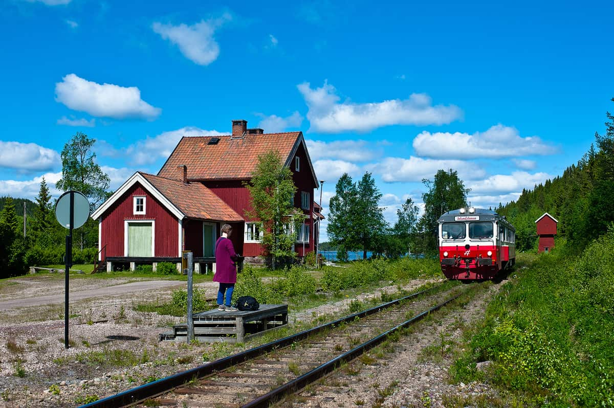 A train approaches Tandsjöborg station to pick up a passenger.