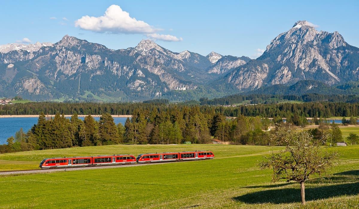 Eine Regionalbahn vor der herrlichen Kulisse von Neuschwanstein und Bayrischen Alpen auf dem Weg nach Füssen.